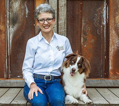 Lisa Waggoner with dog and wood background