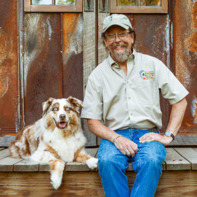 Brad with dog in front of barn